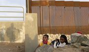 A Haitian migrant family looks to emerge from a rocky canal adjacent to a gap in the U.S. border wall in Yuma, Ariz., Wednesday, June 9, 2021. (AP Photo/Eugene Garcia)