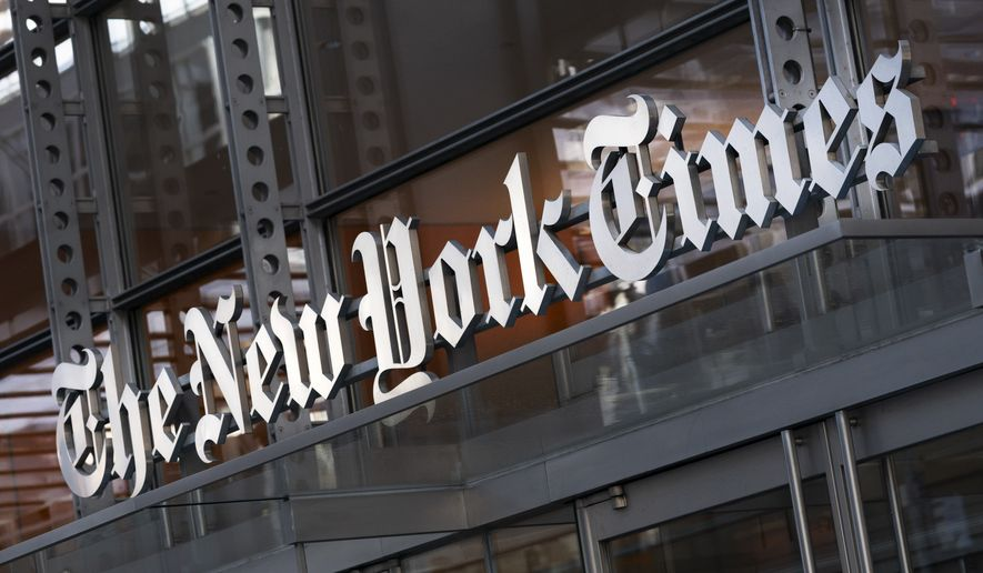 In this Thursday, May 6, 2021, file photo, a sign for The New York Times hangs above the entrance to its building, in New York. (AP Photo/Mark Lennihan, File)