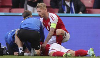 Denmark's Christian Eriksen lays on the ground after collapsing during the Euro 2020 soccer championship group B match between Denmark and Finland at Parken stadium in Copenhagen, Denmark, Saturday, June 12, 2021. (Friedemann Vogel/Pool via AP)