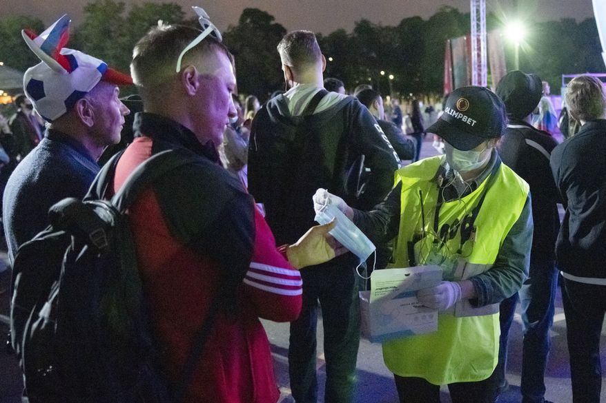 A member of the security personnel distributes face masks as supporters of Russia's team watch the Euro 2020 soccer championship group B match between Russia and Belgium at a fan area in the Luzhniki Olympic Complex in Moscow, Russia, Saturday, June 12, 2021. (AP Photo/Pavel Golovkin)