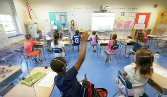 In this May 18, 2021, file photo, a teacher, center, and her third grade students wear face masks and are seated at proper social distancing spacing during as she conducts her class in Rye, N.Y. In response to a push for culturally responsive teaching that gained steam following last year's police killing of George Floyd, Republican lawmakers and governors have championed legislation to limit the teaching of material that explores how race and racism influence American politics, culture and law. The measures have become law in Tennessee, Idaho and Oklahoma and bills have been introduced in over a dozen other states. (AP Photo/Mary Altaffer, File)