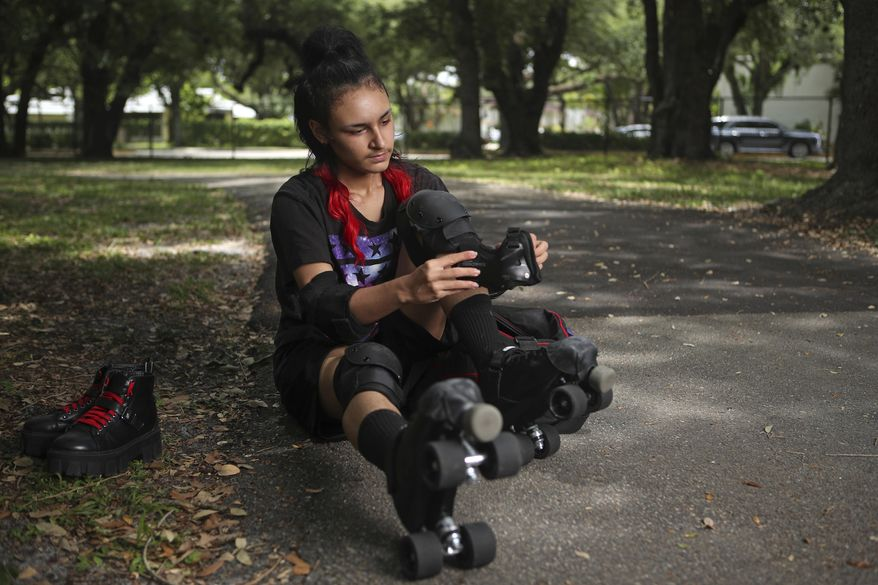 Oliver Echevarria puts on pads to roller skate, May 31, 2021, in Hollywood, Fla. Echevarria was 13 when he came out as transgender. He quit track and field in middle school because of the bullying and discrimination he endured as a young transgender athlete, both on and off the team, he said. (John McCall/South Florida Sun-Sentinel via AP)