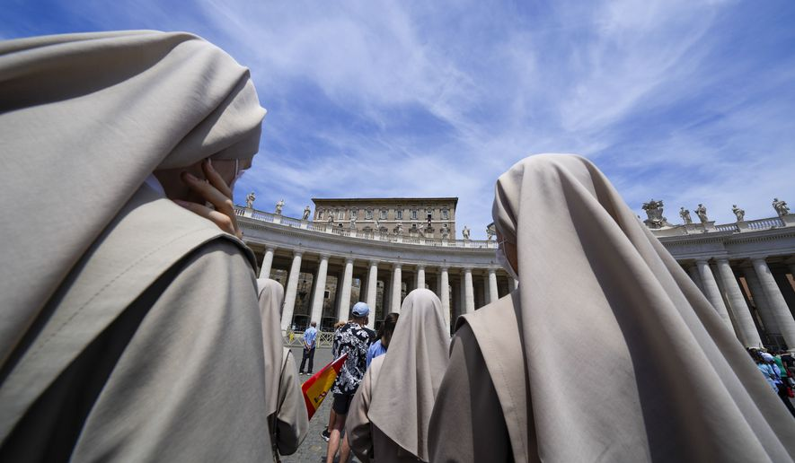 Nuns look at Pope Francis, top right, as he recites the Angelus noon prayer from the window of his studio overlooking St. Peter's Square, at the Vatican, Sunday, June 13, 2021. Francis demanded during his speech for humanitarian aid to reach residents of the war-torn Tigray region of northern Ethiopia, where Ethiopian and Eritrean soldiers are blocking food and other assistance. (AP Photo/Andrew Medichini)