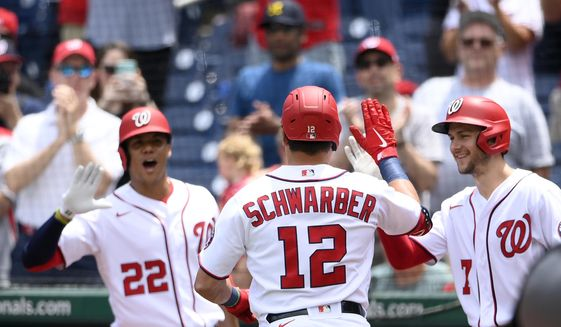 Washington Nationals' Kyle Schwarber celebrates his home run with Trea Turner (7) and Juan Soto (22) during the first inning of a baseball game against the San Francisco Giants, Sunday, June 13, 2021, in Washington. (AP Photo/Nick Wass)