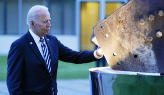 President Joe Biden touches a piece of steel from the North Tower of the World Trade Center while visiting a memorial to the September 11 terrorist attacks at NATO headquarters in Brussels, Monday, June 14, 2021. (AP Photo/Patrick Semansky)