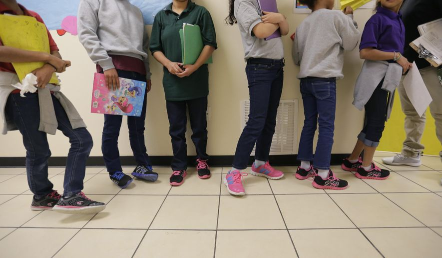 """In this Aug. 29, 2019, photo, migrant teens line up for a class at a """"tender-age"""" facility for babies, children and teens, in Texas' Rio Grande Valley, in San Benito, Texas. A federal volunteer at the Biden administration's largest shelter for unaccompanied immigrant children says paramedics were called regularly during her the two weeks she worked there. She said panic attacks would occur often after some of the children were taken away to be reunited with their families, dashing the hopes of those left behind. The conditions described by the volunteer highlight the stress of children who cross the U.S.-Mexico border alone and now find themselves held at unlicensed mass-scale facilities waiting to reunite with relatives. (AP Photo/Eric Gay) **FILE**"""
