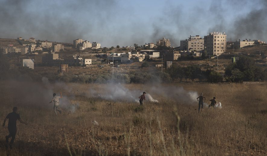 Israeli soldiers use teargas to disperse Palestinian protesters during clashes at the entrance the Jewish settlement of Beit El, near the West Bank city of Ramallah, background, Tuesday, June. 15, 2021. (AP Photo/Nasser Nasser)