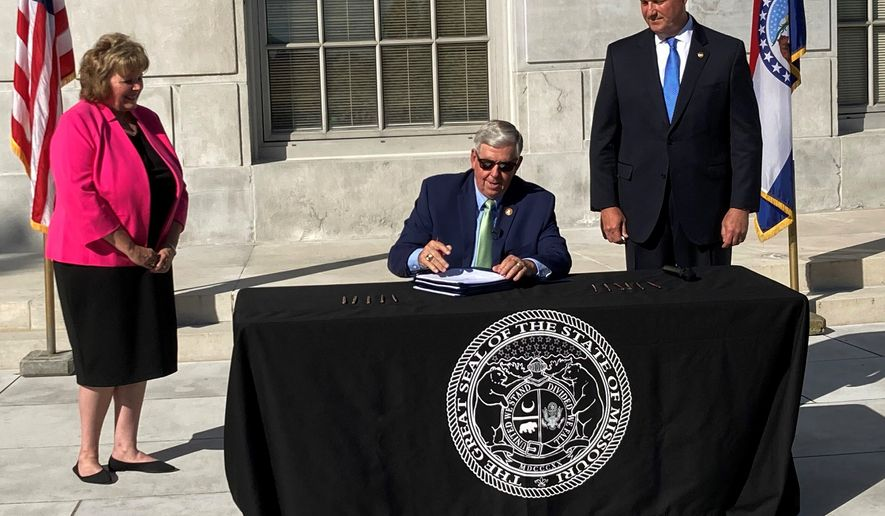 Missouri Gov. Mike Parson signs legislation limiting the during of local public health orders during a ceremony Tuesday, June 15, 2021, outside the state Capitol in Jefferson City, Mo. The new law took effect immediately and was passed in response to local restrictions imposed during the coronavirus pandemic. Among its supporters were state Sen. Sandy Crawford, left, and House Speaker Pro Tem John Wiemann. (AP Photo/David A. Lieb)