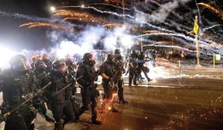 In this Sept. 5, 2020, file photo, police use chemical irritants and crowd control munitions to disperse protesters during a demonstration in Portland, Ore. Authorities said Tuesday, June 15, 2021, a grand jury returned an indictment against a Portland police officer, accusing him of hitting a protester in the head with a baton in 2020. The city saw widespread, often violent protests following the police killing of George Floyd. (AP Photo/Noah Berger, File)