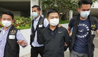 Ryan Law, second from right, Apple Daily's chief editor, is arrested by police officers in Hong Kong Thursday, June 17, 2021. Hong Kong police on Thursday morning arrested the chief editor and four other senior executives of Apple Daily under the national security law on suspicion of collusion with a foreign country to endanger national security, according to local media reports. Local media, including the South China Morning Post and Apple Daily, reported Thursday that national security police arrested Apple Daily's chief editor Ryan Law. (AP Photo)