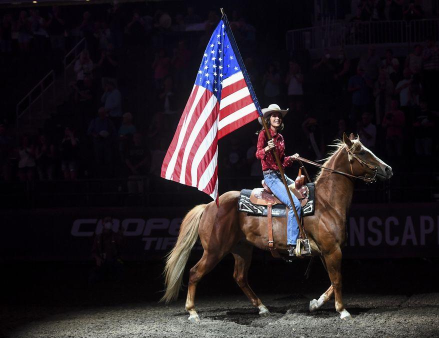 South Dakota Gov. Kristi Noem presents the U.S. flag before the national anthem on July 11, 2020, at the Denny Sanford Premier Center in Sioux Falls, S.D. (Abigail Dollins/The Argus Leader via AP)