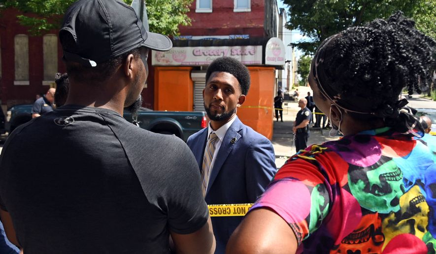 Baltimore Mayor Brandon Scott arrives at the scene where police investigate a shooting, Wednesday, June 16, 2021, in Baltimore. One person was killed and five others were wounded Wednesday when gunmen walked up a street and opened fire on a Baltimore block from an intersection, the city's police commissioner said. (Kim Hairston/The Baltimore Sun via AP)