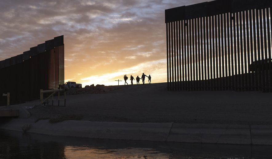 In this Thursday, June 10, 2021, file photo, a pair of migrant families from Brazil pass through a gap in the border wall to reach the United States after crossing from Mexico to Yuma, Arizona, to seek asylum. (AP Photo/Eugene Garcia, File)