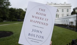 """FILE - In this June 18, 2020, file photo a copy of """"The Room Where It Happened,"""" by former national security adviser John Bolton, is photographed at the White House in Washington. The Justice Department has abandoned its lawsuit against former Trump administration national security adviser John Bolton over a book that officials argued disclosed classified information, and prosecutors have also dropped a grand jury investigation over the book's publication. (AP Photo/Alex Brandon, File)"""