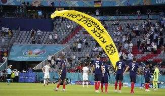 A Greenpeace paraglider lands on the pitch before the Euro 2020 soccer championship group F match between France and Germany at the Allianz Arena in Munich, Germany, Tuesday, June 15, 2021. (AP Photo/Matthias Schrader, Pool)