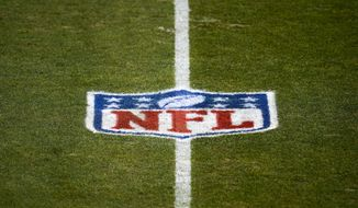This Jan. 3, 2021, file photo shows the NFL logo on the field before a game between the Denver Broncos and the Las Vegas Raiders in Denver. The NFL and NFL Players Association have updated COVID-19 protocols to loosen restrictions for fully vaccinated players and to encourage others to get the vaccine.Unvaccinated players must continue to get daily testing, wear masks and practice physical distancing. They won't be allowed to eat meals with teammates, can't participate in media or marketing activities while traveling, aren't permitted to use the sauna or steam room and may not leave the team hotel or interact with people outside the team while traveling. (AP Photo/Jack Dempsey, File) **FILE**