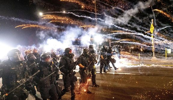 In this Sept. 5, 2020, photo, police use chemical irritants and crowd control munitions to disperse protesters during a demonstration in Portland, Ore. City officials insist Portland is resilient as they launch a revitalization plan — in the form of citywide cleanups of protest damage, aggressive encampment removals, increased homeless services and police reform — to repair its reputation. (AP Photo/Noah Berger) **FILE**