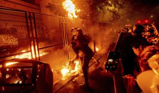"""In this July 22, 2020, file photo, protesters throw flaming debris over a fence at the Mark O. Hatfield United States Courthouse in Portland, Ore. Until a year ago, the city was best known nationally for its ambrosial food scene, craft breweries and """"Portlandia"""" hipsters. Now, months-long protests following the killing of George Floyd, a surge in deadly gun violence, and an increasingly visible homeless population have many questioning whether Oregon's largest city can recover.(AP Photo/Noah Berger)"""