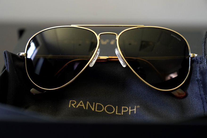 A pair of Randolph Engineering Concorde teardrop sunglasses, in 23-karat gold finish with polarized American gray lenses, rest on a table at the company where they are made, in Randolph, Mass., Thursday, June 17, 2021. Russian President Vladimir Putin received a pair of the sunglasses from President Joe Biden following their meeting in Switzerland this week. (AP Photo/Steven Senne)