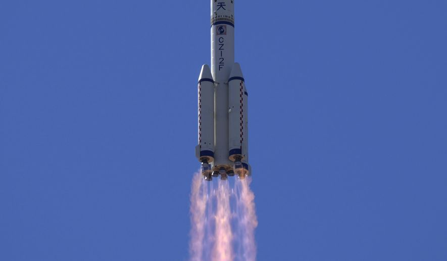 In this file photo, a Long March-2F Y12 rocket carrying a crew of Chinese astronauts in a Shenzhou-12 spaceship lifts off at the Jiuquan Satellite Launch Center in Jiuquan in northwestern China, Thursday, June 17, 2021. (AP Photo/Ng Han Guan)