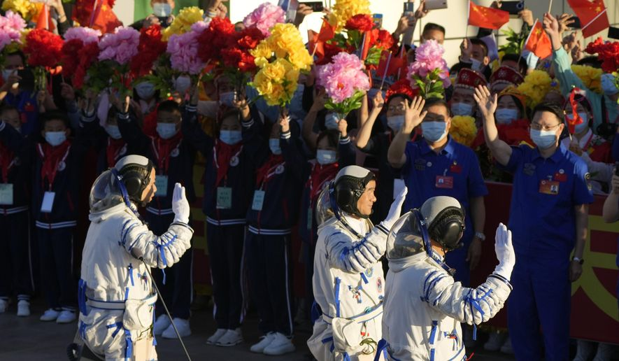 Chinese astronauts wave as they prepare to board for liftoff at the Jiuquan Satellite Launch Center in Jiuquan in northwestern China, Thursday, June 17, 2021. China plans on Thursday to launch three astronauts onboard the Shenzhou-12 spaceship who will be the first crew members to live on China's new orbiting space station Tianhe, or Heavenly Harmony. (AP Photo/Ng Han Guan)