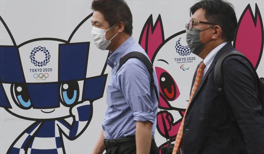 People walk by posters to promote the Olympic Games planned to start in the summer of 2021, in Tokyo, Wednesday, June 16, 2021. (AP Photo/Koji Sasahara)