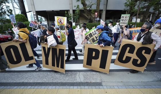 In this May 9, 2021, file photo, people who are against the Tokyo 2020 Olympics set to open in July, march to protest around Tokyo's National Stadium during an anti-Olympics demonstration. Public sentiment in Japan has been generally opposed to holding the Tokyo Olympics and Paralympics. This is partly based of fears the coronavirus will spike as almost 100,000 people — athletes and others — enter for both events.(AP Photo/Eugene Hoshiko, File) **FILE**