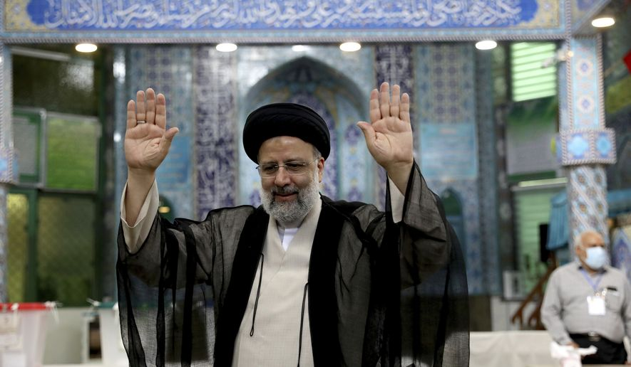 Ebrahim Raisi, a candidate in Iran's presidential elections, raises his hands as he casts his vote at a polling station in Tehran, Iran, Friday, June 18, 2021. Iran began voting Friday in a presidential election tipped in the favor of a hard-line protege of Supreme Leader Ayatollah Ali Khamenei, fueling public apathy and sparking calls for a boycott in the Islamic Republic. (AP Photo/Ebrahim Noroozi)