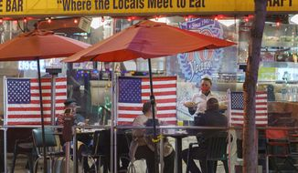 In this Nov. 24, 2020, photo, a waitress serves patrons sitting outdoors for dinner separated by plastic dividers with national flags at Mel's drive-in restaurant on Sunset Boulevard in West Hollywood, Calif. California has now regained more than half of the 2.7 million jobs it lost at the start of the pandemic, state officials said Friday, June 17, 2021, a trend driven by restaurants and hotels hiring more people as the state gradually reopens its economy. (AP Photo/Damian Dovarganes) **FILE**