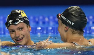 Katie Ledecky congratulates Katie Grimes after the women's 800 freestyle during wave 2 of the U.S. Olympic Swim Trials on Saturday, June 19, 2021, in Omaha, Neb. (AP Photo/Jeff Roberson)