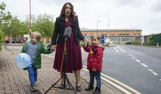 """Stella Moris stands with her children Gabriel, four, left, and Max, two, as she speaks to the media, outside Belmarsh Prison, following a visit to her partner and their father Julian Assange in London, Saturday June 19, 2021.  Assange is being detained in Belmarsh prison in London while the US continues an attempt to extradite him under the US's 1917 Espionage Act for """"unlawfully obtaining and disclosing classified documents related to the national defence"""". (Dominic Lipinski/PA via AP)"""