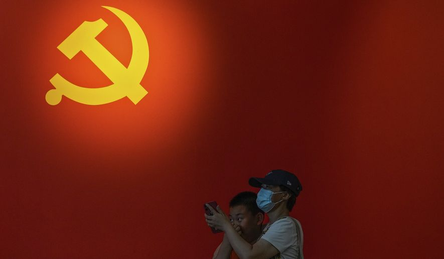 A woman wearing a face mask to help curb the spread of the coronavirus and a child stand near a Communist Party's flag on display at an exhibition promoting China's achievement under communist party from 1921 to 2021, in Beijing, Sunday, June 20, 2021. Authorities are gearing up to mark the 100th anniversary of the founding of China's ruling Communist Party, which will be observed on July 1. (AP Photo/Andy Wong)