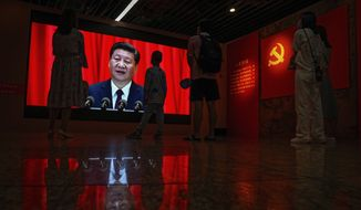 Visitors watch a screen showing Chinese President Xi Jinping speaking next to a Communist Party's flag, at an exhibition promoting China's achievement under communist party from 1921 to 2021, in Beijing, Sunday, June 20, 2021. Authorities are gearing up to mark the 100th anniversary of the founding of China's ruling Communist Party, which will be observed on July 1. (AP Photo/Andy Wong)