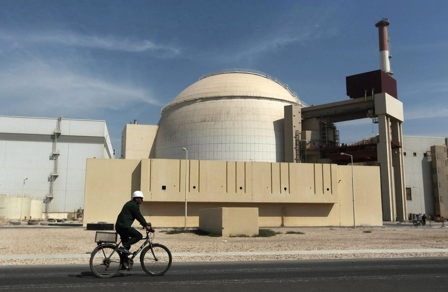"""In this Oct. 26, 2010, file photo, a worker rides a bicycle in front of the reactor building of the Bushehr nuclear power plant, just outside the southern city of Bushehr. Iran's sole nuclear power plant has undergone a temporary emergency shutdown, state TV reported on Sunday, June 20, 2021. An official from the state electric energy company, Gholamali Rakhshanimehr, said on a talk show that the Bushehr plant shutdown began on Saturday and would last """"for three to four days."""" (AP Photo/Mehr News Agency, Majid Asgaripour, File)"""