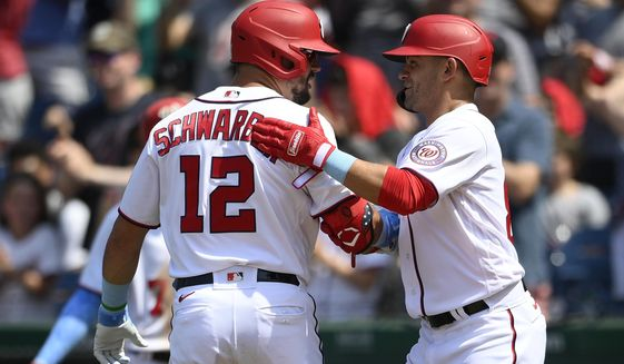 Washington Nationals' Kyle Schwarber (12) celebrates his two-run home run with Gerardo Parra, right, during the seventh inning of a baseball game against the New York Mets, Sunday, June 20, 2021, in Washington. (AP Photo/Nick Wass)
