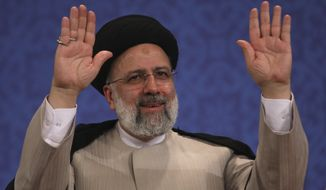 Iran's new President-elect Ebrahim Raisi waves to participants at the conclusion of his press conference in Tehran, Iran, Monday, June 21, 2021. Raisi said Monday he wouldn't meet with President Joe Biden nor negotiate over Tehran's ballistic missile program and its support of regional militias, sticking to a hard-line position following his landslide victory in last week's election. (AP Photo/Vahid Salemi)