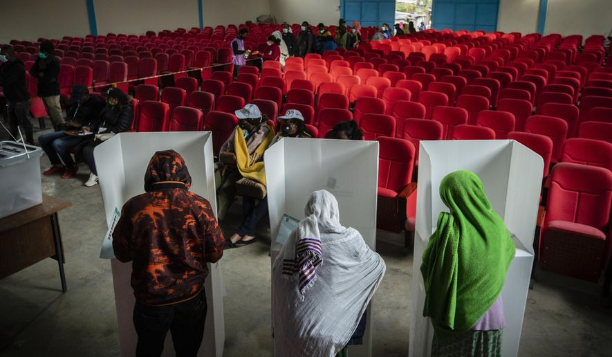 Ethiopians cast their votes in the general election at a polling center in the capital Addis Ababa, Ethiopia, Monday, June 21, 2021. Ethiopia was voting Monday in the greatest electoral test yet for Prime Minister Abiy Ahmed as insecurity and logistical issues meant ballots wouldn't be cast in more than 100 constituencies of the 547 across the country. (AP Photo/Ben Curtis)