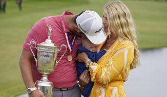 Jon Rahm, of Spain, holds the champions trophy for photographers as he stands with his wife, Kelley Rahm and kisses their child, Kepa Rahm, 11 months, after the final round of the U.S. Open Golf Championship, Sunday, June 20, 2021, at Torrey Pines Golf Course in San Diego. (AP Photo/Marcio Jose Sanchez) **FILE**