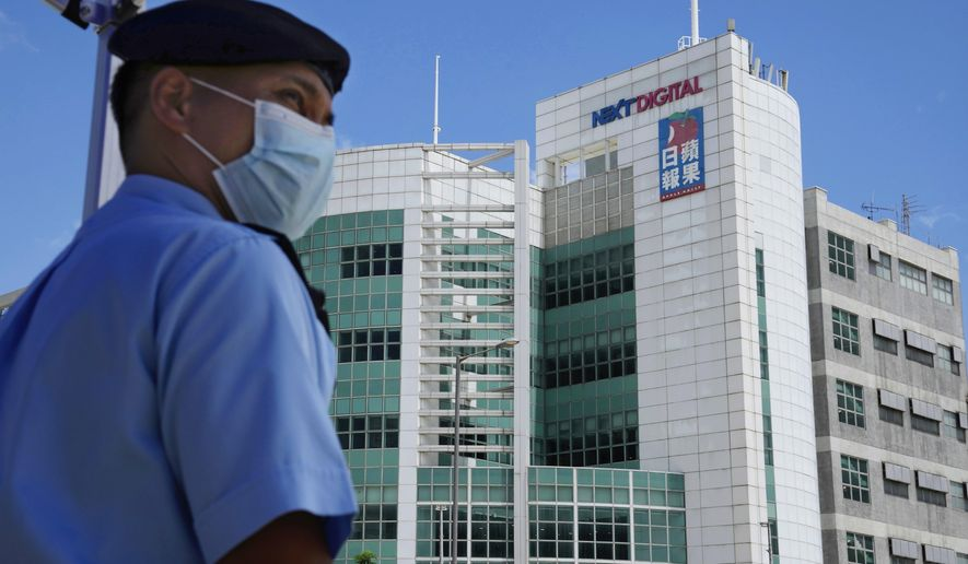 In this Thursday, June 17, 2021, file photo, a police officer stands guard outside the Apple Daily headquarters in Hong Kong after arresting the chief editor and four other senior executives of the newspaper under the national security law on suspicion of collusion with a foreign country to endanger national security. Hong Kong pro-democracy newspaper Apple Daily said in a news report Monday, June 21, 2021, that its board of directors has requested authorities to unfreeze some assets so that it could pay wages. (AP Photo/Kin Cheung, File)