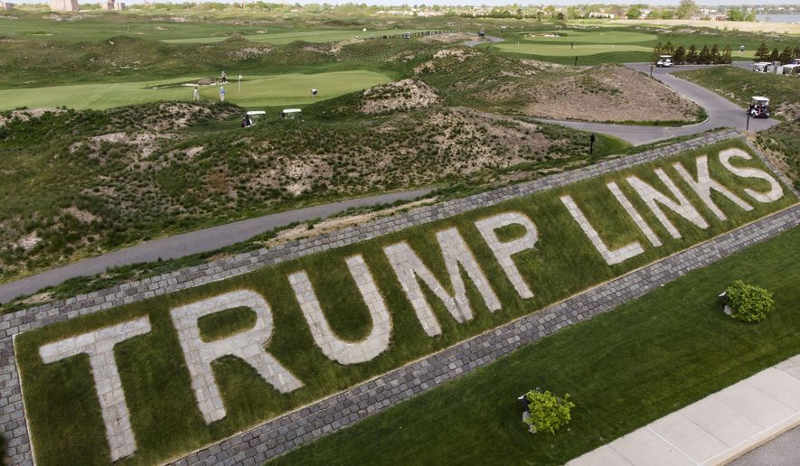 Patrons play the links as a giant branding sign is displayed with flagstones at Trump Golf Links at Ferry Point in the Bronx borough of New York on Tuesday, May 4, 2021. (AP Photo/John Minchillo, File)