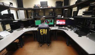 In this Tuesday, July 31, 2018, photo, an FBI employee works in a computer forensics lab at the FBI field office in New Orleans. More than 20 people working for the FBI headquarters in Louisiana are working on cyber security. They include experts working at forensics labs, doing forensics on computer hard drives and developing techniques for analyzing computer memories in efforts to fight and find intruders, according to the special agent in charge of the FBI's New Orleans field office. (AP Photo/Gerald Herbert)