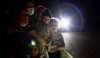 FILE - In this May 17, 2021 file photo, a group of migrants mainly from Honduras and Nicaragua wait along a road after turning themselves in upon crossing the U.S.-Mexico border, in La Joya, Texas. The U.S. Homeland Security Department says thousands of asylum-seekers whose claims were dismissed or denied under a Trump administration policy that forced them to wait in Mexico for their court hearings will be allowed to return for another chance at humanitarian protection. (AP Photo/Gregory Bull, File)