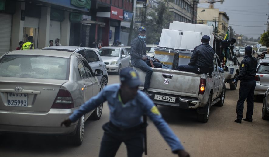 Armed police, seen through vehicle exhaust fumes, provide security for electoral materials as they are transported from a polling station in the capital Addis Ababa, Ethiopia Tuesday, June 22, 2021, a day after the country voted in a general election. Ethiopia voted Monday in the greatest electoral test yet for Prime Minister Abiy Ahmed as insecurity and logistical issues meant ballots wouldn't be cast in more than 100 constituencies of the 547 across the country. (AP Photo/Ben Curtis)