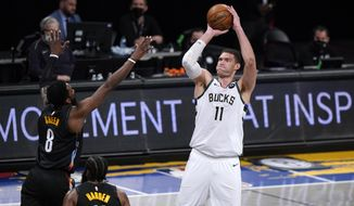 Milwaukee Bucks center Brook Lopez (11) shoots over Brooklyn Nets forward Jeff Green (8) and guard James Harden (13) during the first half of Game 5 of a second-round NBA basketball playoff series Tuesday, June 15, 2021, in New York. (AP Photo/Kathy Willens) **FILE**