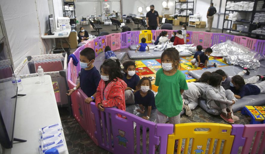 In this March 30, 2021, photo, young unaccompanied migrants, from ages 3 to 9, watch television inside a playpen at the U.S. Customs and Border Protection facility, the main detention center for unaccompanied children in the Rio Grande Valley, in Donna, Texas. On Monday, June 21, 2021, more than a dozen immigrant children described difficult conditions, feelings of isolation and a desperation to get out of emergency facilities set up by the Biden administration to cope with a rise in the arrival of minors on the southwest border. (AP Photo/Dario Lopez-Mills, Pool) **FILE**