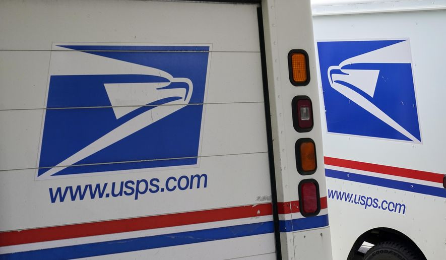 In this Aug. 18, 2020, photo, mail delivery vehicles are parked outside a post office in Boys Town, Neb. (AP Photo/Nati Harnik) **FILE**