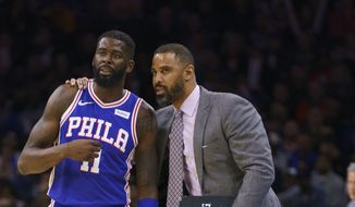 This Nov. 20, 2019, file photo shows Philadelphia 76ers' James Ennis III, left, talking things over with assistant coach Ime Udoka, right, during the second half of an NBA basketball game against the New York Knicks, in Philadelphia.  The Boston Celtics have hired Brooklyn Nets assistant Ime Udoka to be their new coach, a person familiar with the decision told The Associated Press on Wednesday, June 23, 2021. The person spoke on the condition of anonymity because the deal had not been announced. (AP Photo/Chris Szagola, File) **FILE**