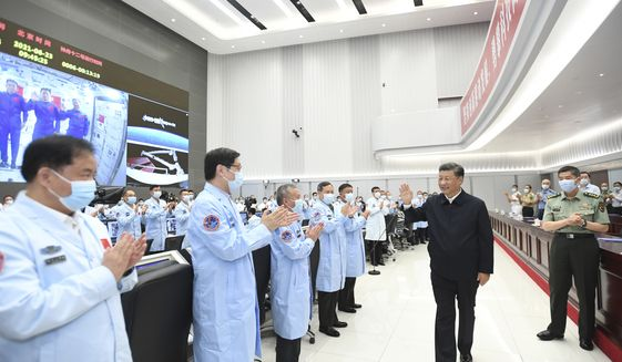 In this photo released by China's Xinhua News Agency, Chinese President Xi Jinping greets workers after having a video conversation with the three astronauts aboard China's space station core module Tianhe at the Beijing Aerospace Control Center in Beijing, Wednesday, June 23, 2021. (Yan Yan/Xinhua via AP)  **FILE**
