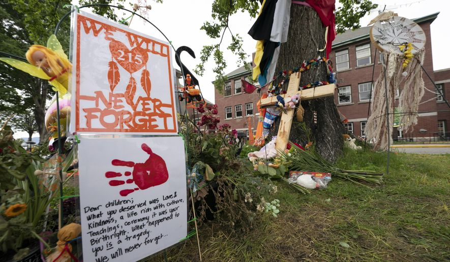 Signs are pictured at a memorial outside the Residential School in Kamloops, British Columbia., Sunday, June 13, 2021. The remains of 215 children were discovered buried near the former Kamloops Indian Residential School earlier this month. (Jonathan Hayward/The Canadian Press via AP) ** FILE **