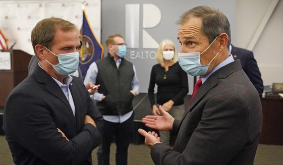 FILE - In this Nov. 3, 2020, file photo, Republican Reps. Chris Stewart, left, and John Curtis talk during an Utah Republican election night party in Sandy, Utah. Curtis is leading a new Conservative Climate Caucus for House Republicans. The group wants to educate fellow Republicans about global warming and develop market-based policies to counter Green New Deal and other Democratic proposals. (AP Photo/Rick Bowmer, File)
